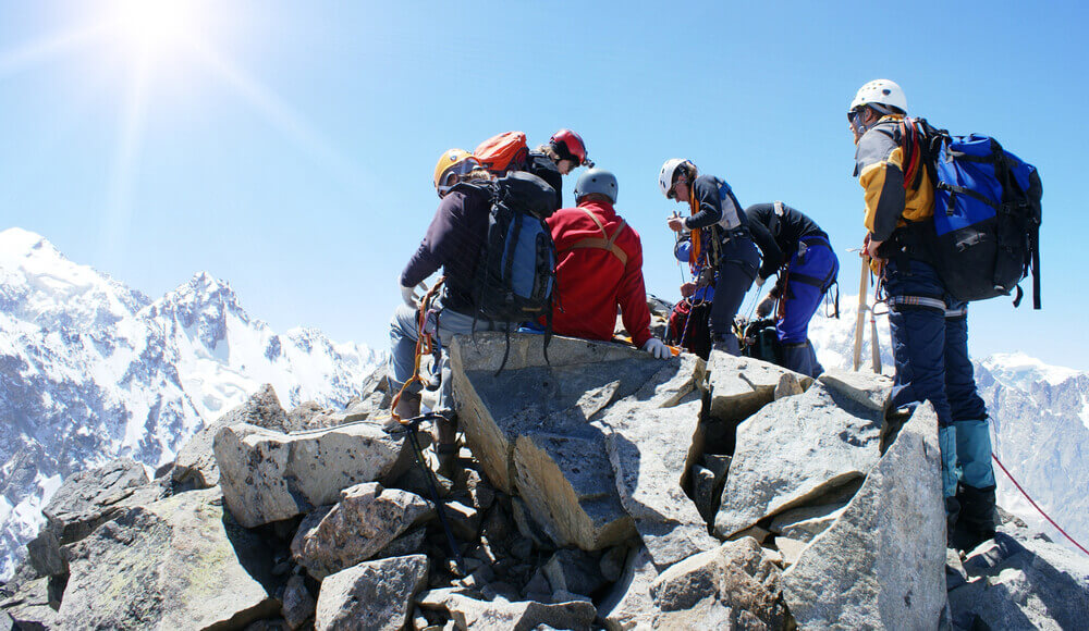 Group of mountain climbers on the top of mountain.