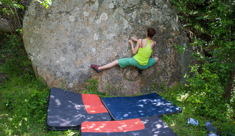 Beginner outdoor bouldering climber use crash pad for safety protection.
