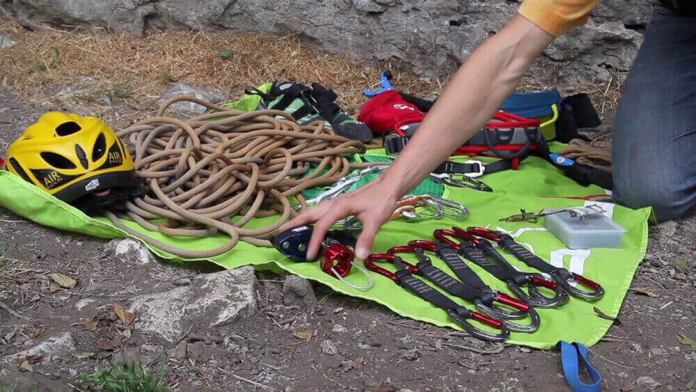 Climber introducing and lay out his rock climbing gear and equipment on the floor.
